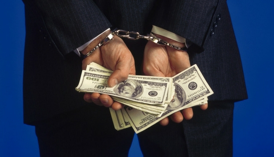 a businessman handcuffed holding cash